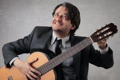 Zakenman die de gitaar stemmen Stock Foto's