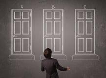 Zakenman die de juiste deur kiezen Stock Afbeelding