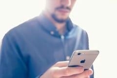 Zakenman die de nieuwe Apple-iPhone6s retina houden stock fotografie