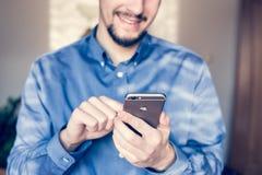 Zakenman die de nieuwe Apple-iPhone6s retina houden Stock Foto's