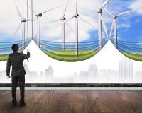Zakenman die de open bedekte grijze stad van windturbines gordijn trekken Royalty-vrije Stock Foto's