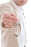 Zakenman die de sleutels van nieuw huis houdt Stock Afbeeldingen