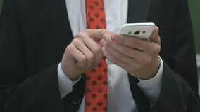 Zakenman die de tekst schrijven die een smartphone gebruiken stock footage