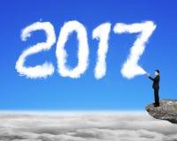 Zakenman die de witte vorm van de het jaarwolk van 2017 in hemel bespuiten Stock Afbeelding