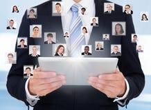 Zakenman die digitale tablet gebruiken die mededeling vertegenwoordigen Stock Afbeeldingen