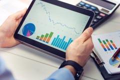 Zakenman die digitale tablet met grafieken en grafiekenrapport houden royalty-vrije stock foto