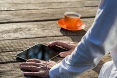 Zakenman die digitale tablet op rustiek houten bureau gebruiken royalty-vrije stock afbeeldingen