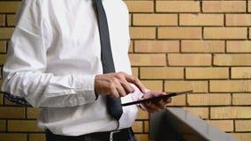Zakenman die digitale tabletcomputer houden, die zich bij het bureaubalkon bevinden met gele bakstenen muur stock video