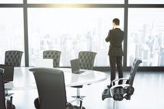 Zakenman die door een venster in de conferentieruimte kijken met Stock Foto's