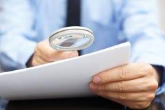 Zakenman die door een vergrootglas aan contract kijken Stock Foto's