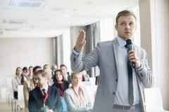 Zakenman die door microfoon tijdens seminarie in overeenkomstcentrum spreken Stock Foto