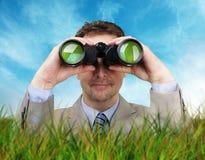 Zakenman die door verrekijkers kijkt Stock Fotografie
