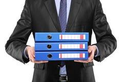 Zakenman die drie blauwe omslagen houdt Stock Afbeeldingen