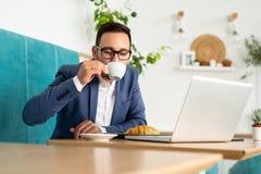 Zakenman die e-mail controleren en koffie drinken royalty-vrije stock fotografie