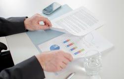 Zakenman die economische documenten analyseren Stock Afbeelding