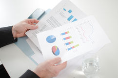 Zakenman die economische documenten analyseren Stock Fotografie