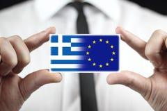 Zakenman die een adreskaartje met de Vlag van Griekenland houden en de EU- Stock Foto