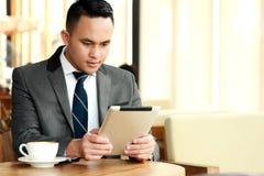 Zakenman die een artikel op zijn tabletten lezen royalty-vrije stock fotografie