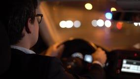 Zakenman die een auto in de handen van de nachtstad op het wiel drijven stock video