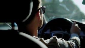 Zakenman die een auto in de stad in daglicht drijven stock video