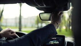 Zakenman die een auto drijven en achteruitkijkspiegel onderzoeken voorraad Zakenman in de auto die in de achtermening kijken stock videobeelden
