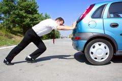 Zakenman die een auto duwt Stock Foto