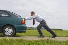 Zakenman die een auto duwt Stock Foto's