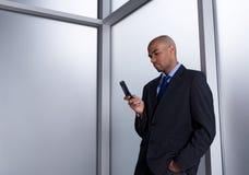 Zakenman die een bericht met zijn celtelefoon verzendt stock foto's
