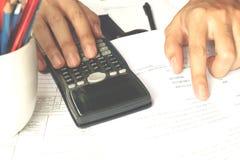 Zakenman die een calculator gebruiken om de aantallen te berekenen Boekhouding Royalty-vrije Stock Foto