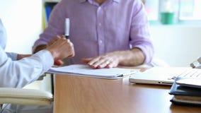 Zakenman die een contract ondertekenen en handen met onderneemster schudden stock footage