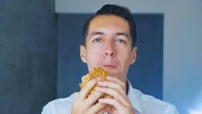 Zakenman die een hamburger eten Snel voedsel Cheeseburger, hamburger, sandwich stock video
