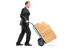 Zakenman die een handvrachtwagen met dozen duwt Royalty-vrije Stock Foto