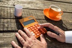 Zakenman die een kleurrijke oranje handcalculator gebruiken royalty-vrije stock fotografie