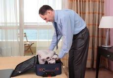 Zakenman die een koffer inpakt Stock Foto's