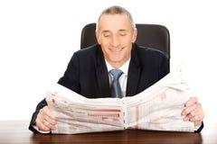 Zakenman die een krant in het bureau lezen Stock Afbeelding