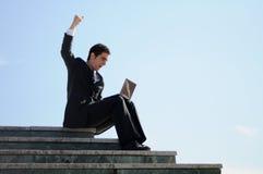 Zakenman die een laptop computer houdt Stock Afbeelding