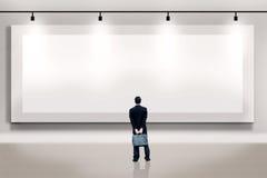 Zakenman die een leeg aanplakbord bekijkt Stock Foto