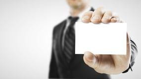 Zakenman die een leeg adreskaartje overhandigt Stock Foto