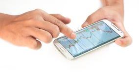 Zakenman die een mobiel apparaat met behulp van om voorraden en markt te controleren dat stock foto