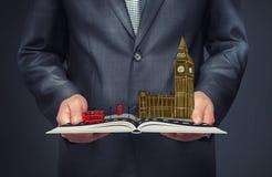 Zakenman die een open boek met een schets van Londen op de bovenkant houden royalty-vrije stock afbeelding