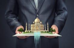 Zakenman die een open boek met schets van Taj Mahal op de bovenkant houden stock afbeelding