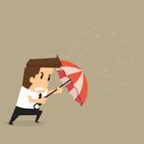 Zakenman die een paraplu in het midden van een stortbui houden Stock Afbeeldingen