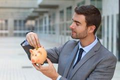 Zakenman die een piggybank gebruiken om geld te besparen royalty-vrije stock afbeeldingen
