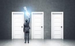 Zakenman die een reuzesleutel houden dichtbij deuren Stock Foto