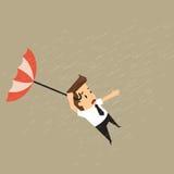 Zakenman die een slagparaplu in het midden van een stortbui houden Royalty-vrije Stock Afbeeldingen