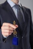 Zakenman die een sleutel aanbiedt Stock Foto