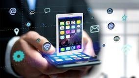 Zakenman die een smartphone met tablet het omringen gebruiken door app Royalty-vrije Stock Afbeelding