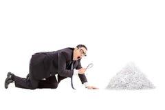 Zakenman die een stapel van verscheurd document bekijken Stock Fotografie