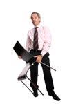 Zakenman die een stoel houdt stock afbeelding
