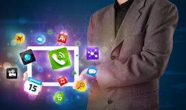 Zakenman die een tablet met moderne kleurrijke apps en pictogrammen houden Stock Fotografie